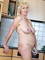 Busty old woman with wide hips gives her clit a treat in the kitchen